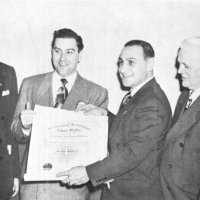 "1/13/51: Presentation of Charter to the Geneva-Excelsior Lions Club. L to R: John J. McDonald, Past District Governor (District 4, 1928-29); Maurice Perstein, Deputy District Governor; Charter President ""Murphy"" Boehme; District Governor Joseph R. Territo (4-B2); Thomas S. Neilson (4-B Past International Director (1942-44); and Jack Merchant, Past District Governor (4-B, 1949-50)."
