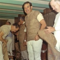 Early 1971 - Dress rehearsal for the District 4-C4 Convention in May at a member's home - Member (blue shirt in back), member (bending putting on burlap sack), Lions Joe Giuffre (facing away from camera), Art Blum, and Bob Dobbins, all getting dress for convention rehearsal.