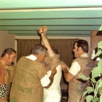Early 1971 - Dress rehearsal for the District 4-C4 Convention in May at a member's home - L to R: Lion Frank Ferrera gets a good chuckle while Lions Joe Giuffre and Art Blum help another member squeeze into his burlap sack.
