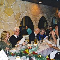 12/8/04 - Club Christmas Party, Ristorante Mar, Pacifica - Members and guests singing Christmas carols, led by Lion Handford standing). From left: guest, Lion Al Gentile, Lion Ted and Vernelle Wildenradt, and a guest. Lion Charlie Bottarini is seated just below Lion Handford.
