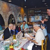 12/8/04 - Club Christmas Party, Ristorante Mar, Pacifica - Members and guests singing Christmas carols, led by Lion Handford (standing). From left: Lion Al Gentile, Lion Ted and Vernelle Wildenradt, and a guest couple. Lion Charlie and Estelle Bottarini are seated just below Lion Handford.