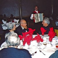 11/27/05 - 27th Annual Giulio Francesconi Charity Raffle Drawing at the Italian American Social Club -  Guest, on left, at the table with Helen and Lion George Habeeb talking with Lion Joe Farrah while accordionist John Fiore plays in the background.