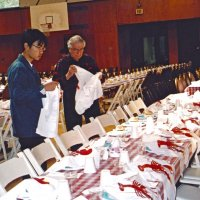 2/25/06 - 24th Annual Crab Feed at the Janet Pomeroy Center For The Handicapped - 470 attendees - Lion Joe Farrah helps a Lowell High School Leo place crab bibs at place setting before the event. Lion Ward Donnelly working in the background.