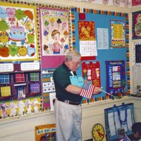 2/17/06 - Flag Day Program at Mission Educational Center for 211 students - Lion Bob Lawhon using the flag handout to tell students about the pledge of allegiance, facts about the flag, and the stars on the flag and the states they represent.