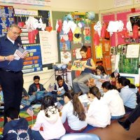 2/17/06 - Flag Day Program at Mission Educational Center for 211 students - Lion Aaron Straus gets close and personal with students while talking about the meaning of the flag and its history. Principal Deborah Molof looks on from the right.