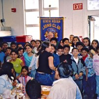 11/22/05 - Mission Educational Center, San Francisco - Students crowd in for a group shot with our Club banner. Lion Bob Lawhon patiently waits next to the banner for them to get set.