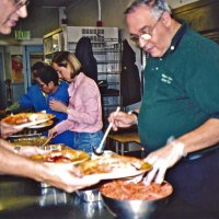 11/22/05 - Mission Educational Center, San Francisco - Lion Lyle Workman, cafeteria staff, and Lions Bre Martinez and Aaron Straus preparing plates for the students.