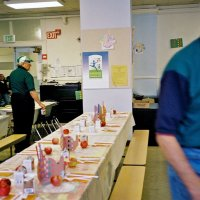 11/22/05 - Mission Educational Center, San Francisco - Lion Joe Farrah, left, making sure all the setting have a carton of milk. Lion Al Gentile, right, hurries to complete the table settings.
