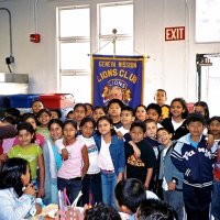 11/22/05 - Mission Educational Center, San Francisco - Students crowd in for a group shot with our Club banner. Lion Bob Lawhon patiently waits just in front of the banner for them to get set.