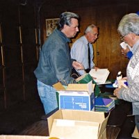 12/15/05 - MEC Christmas at Lion Charlie Bottarini's basement on Moscow St. - l. to r.: Lions Bob Fenech, Ward Donnelly, and Joe Farrah setting up gifts to be distributed to students at the next day's Christmas Party at the Mission Educational Center. Lion Aaron Straus in hiding behind Lion Joe.