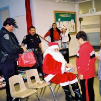 "12/15/06 - Christmas at Mission Educational Center, Police Officer ""Nacho"" Martinez as Santa - Santa greeting students and handing them gifts as his Policer Officers escorts, and others, look on."