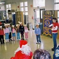 "12/15/06 - Christmas at Mission Educational Center, Police Officer ""Nacho"" Martinez as Santa - Santa, and others, look on as students and their teacher sing a song for them."