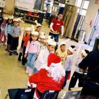 "12/15/06 - Christmas at Mission Educational Center, Police Officer ""Nacho"" Martinez as Santa - Santa greeting each happy student and presenting them with a gift."