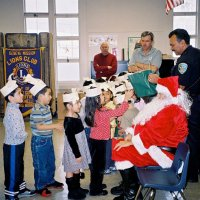 "12/15/06 - Christmas at Mission Educational Center, Police Officer ""Nacho"" Martinez as Santa - Santa, assisted by his Police Officer escorts, greets and presents each student with gifts. Lions Bill Graziano (red sweater) and Bob Fenech look on."