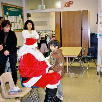 "12/15/06 - Christmas at Mission Educational Center, Police Officer ""Nacho"" Martinez as Santa - Santa greeting a happy student as Lion Bob Fenech, principal Deborah Molof, and others look on."