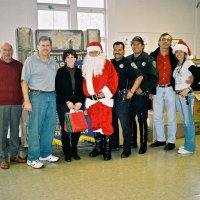 "12/15/06 - Christmas at Mission Educational Center, Police Officer ""Nacho"" Martinez as Santa - Lions Bill Graziano and Bob Fenech, principal Deborah Molof, Santa, his Police Officer escort, and others, all pose after all the presentations are complete."