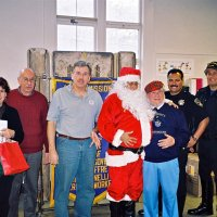 "12/15/06 - Christmas at Mission Educational Center, Police Officer ""Nacho"" Martinez as Santa - Principal Deborah Molof, Lions Bill Graziano and Bob Fenech, Santa, Lion Bob Lawhon, and Santa's Police Officer escorts."