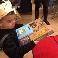 12/21/17 - Christmas with Santa, Mission Educational Center - A very happy school child with his Spanish language book and Hot Wheels received from Santa.