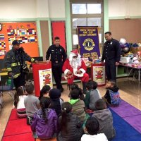 12/21/17 - Christmas with Santa, Mission Educational Center - San Francisco Firemen escort, from the SFFD Toys for Tots Program, look on as Santa talks with the school children.