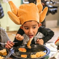 11/16/17 - Serving Thanksgiving Luncheon, Mission Educational Center - An immigrant student wearing a turkey hat feasts on turkey lunch during his first Thanksgiving at Mission Education Center. (Mira Laing/Special to S.F. Examiner)