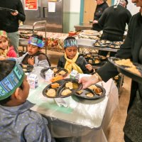 11/16/17 - Serving Thanksgiving Luncheon, Mission Educational Center - Immigrant students are served lunch at their first Thanksgiving at Mission Education Center. (Mira Laing/Special to S.F. Examiner)