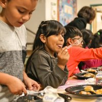 11/16/17 - Serving Thanksgiving Luncheon, Mission Educational Center - Immigrant students feast on lunch at their first Thanksgiving at Mission Education Center. (Mira Laing/Special to S.F. Examiner)