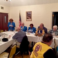 10/17/18 - District Governor's Visitation, Italian American Social Club - L to R outside of table: Lions Al Gentile, Zone Chair Jessie Peoples, Regional Chair Richard Loewen, District Governor Lydia Taylor-Bellinger, President George Salet, and Secretary Joe Farrah. Inside table: Lion Bill Graziano (gray shirt), and visiting Lion Hernaldo Martinez from Pedregal, Panama (in vest.) Lion Zone Chair Jessie Peoples introducing Regional Chair Richard Loewen.