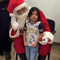 12/18/18 - Los Bomberos Firefighters with Santa at Mission Education Center - Santa posing with a lucky kindergarten student.