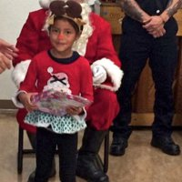 12/18/18 - Los Bomberos Firefighters with Santa at Mission Education Center - A happy kindergarten student, with her gift from Santa.