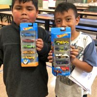 12/18/18 - Los Bomberos Firefighters with Santa at Mission Education Center - two proud first grade students showing off their Hot Wheels gifts from Santa.
