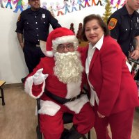 12/18/18 - Los Bomberos Firefighters with Santa at Mission Education Center - Lion Zenaida Lawhon takes a quick pose with Santa between classes.