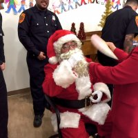 12/18/18 - Los Bomberos Firefighters with Santa at Mission Education Center - Lion Zenaida Lawhon cooling off Santa between classes.