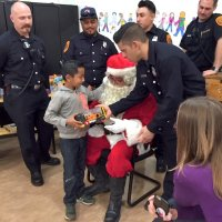 12/18/18 - Los Bomberos Firefighters with Santa at Mission Education Center - A happy third grader receiving his gift from Santa.