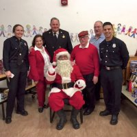12/18/18 - Los Bomberos Firefighters with Santa at Mission Education Center - Santa, some of his crew, and helping Lions Zenaida Lawhon, Bob Lawhon, and President George Salet.