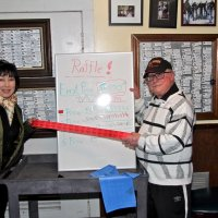 2/23/19 - 34th Annual Crab Feed - Guest Susie Moy with Lion Bob Lawhon, both of whom sold the raffle tickets, displaying the few tickets left and the winning numbers.