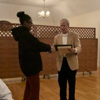 1/15/20 - Student Speaker Contest at the I.A.S.C - Lion Chairman Paul Corvi congratulating student speaker Xiomara Larkin and reading her first runner up certificate to the audiance.